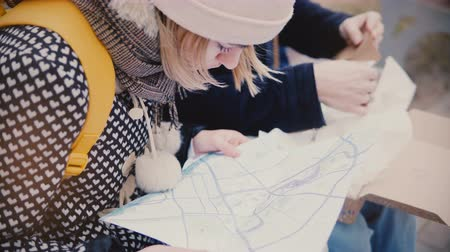 Close-up view of tourist man and woman looking close at a city map travel guide sitting outside together on a winter day Stock Footage