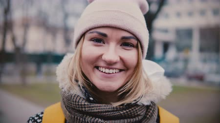 Close-up lifestyle portrait of young beautiful Caucasian girl in winter hat smiling happy, looking at camera on cold day