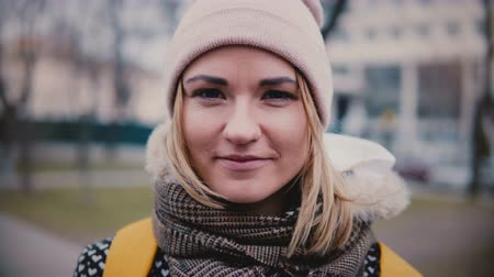 Close-up portrait of young beautiful successful Caucasian freelancer girl in winter hat smiling happy looking at camera. Dostupné videozáznamy