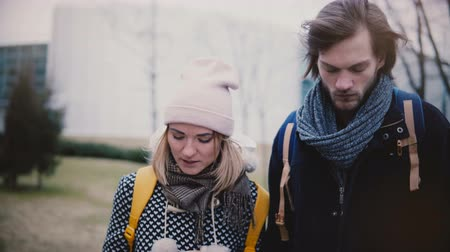 Two happy relaxed Caucasian friends, young man and woman, walking, talking and smiling in the street on cold winter day.