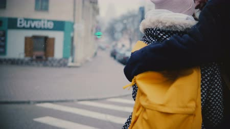Back view happy relaxed young romantic couple in casual warm clothes walk together hugging on a snowy cold winter day.