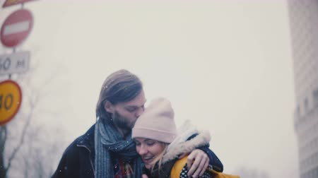 Happy relaxed young romantic couple in casual warm clothes walk together, hug and kiss on a snowy winter Christmas day. Dostupné videozáznamy