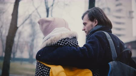 Back view happy relaxed Caucasian young romantic couple in casual winter clothes walk together hugging on a snowy day. Stock Footage