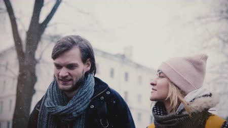 Close-up shot of two happy relaxed Caucasian friends walking, talking and smiling in the street on cold snowy winter day Stock Footage