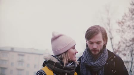 Slow motion happy smiling young European man and woman walk together having fun on a date on a cold snowy winter day.