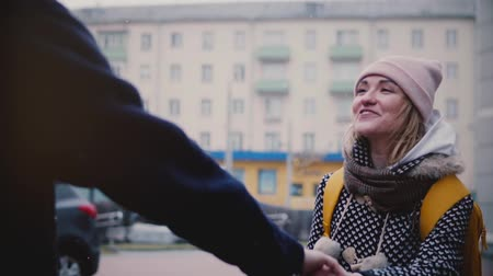 Slow motion happy smiling young European girl in winter clothes walks outside on a date with her boyfriend holding hands