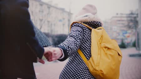 Slow motion happy smiling young European couple walk together on a winter date, girl dragging her boyfriend by the hand. Dostupné videozáznamy