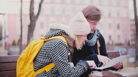 Happy smiling young tourist man and woman sit on a bench together on a winter day looking at a city map travel guide. Dostupné videozáznamy