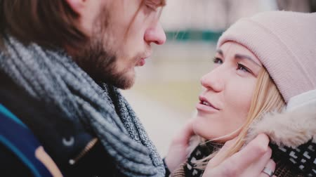 Close-up view of happy smiling young European romantic couple stand close together and talking outside on a cold day. Dostupné videozáznamy
