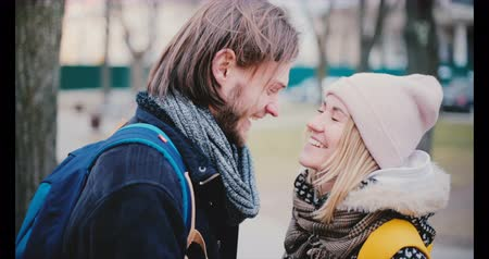 Happy smiling young European romantic couple stand close together looking at each other on a date on a cold winter day.