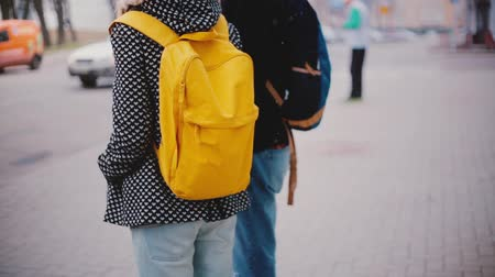 Back view of local man and woman with bright yellow backpack stand close together waiting on a cold snowy winter day.
