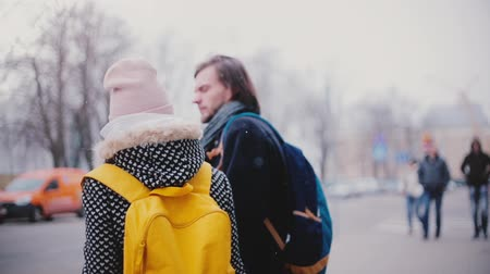 Two happy relaxed Caucasian friends, man and woman, standing together and talking in the street on cold snowy winter day