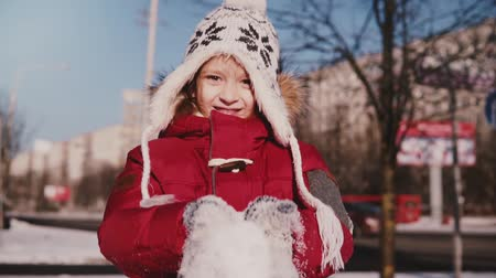 Amazing close-up portrait of fun cute little girl in warm winter clothes throwing snow in the air smiling slow motion. Dostupné videozáznamy