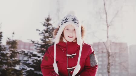 Lovely close-up portrait of cute little Caucasian girl in winter clothes throwing snow in the air having fun slow motion Stock Footage