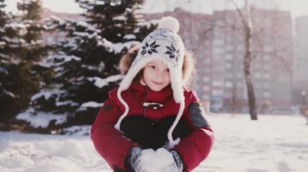 Cute little happy European girl in winter clothes looking at camera, throwing snow in the air and smiling slow motion.