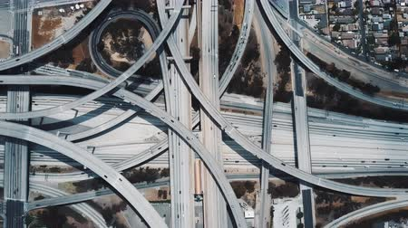 auto estrada : Top view drone rising above incredible complex highway junction in Los Angeles with traffic moving on multiple levels. Vídeos