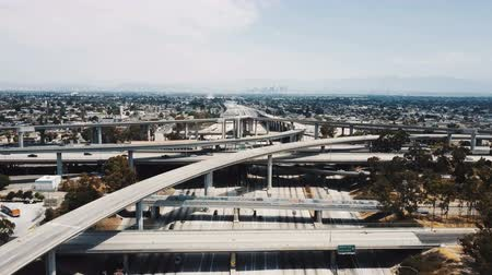 невероятный : Drone flying backwards over large highway interchange in Los Angeles, USA with traffic moving through many road levels. Стоковые видеозаписи
