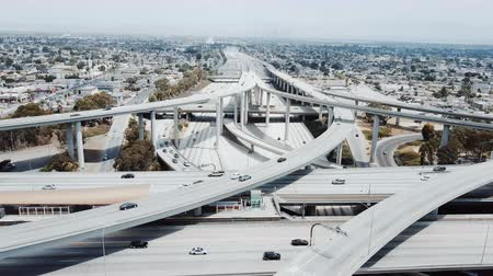 Drone moving backwards over huge freeway intersection in Los Angeles with cars going through many junctions and bridges.