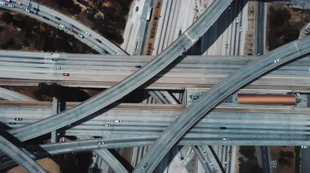 államközi : Drone ascending and spinning fast above large highway road intersection in Los Angeles with cars on multiple flyovers.