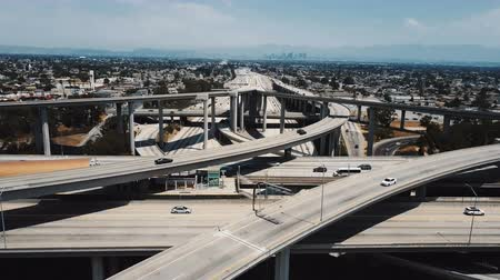 bíró : Drone flying backwards above famous American Judge Pregerson road junction with multiple flyovers, freeways and bridges.