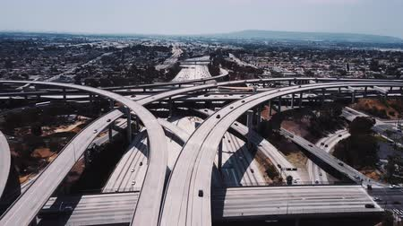 Static drone aerial shot of large complex highway road junction with cars moving through multiple flyovers and bridges.