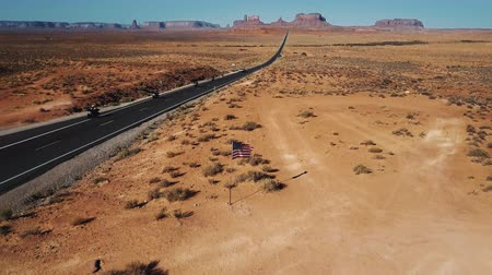 Drone camera tilts up to reveal American flag waving in the middle of Monument Valley, bikers passing by on desert road.