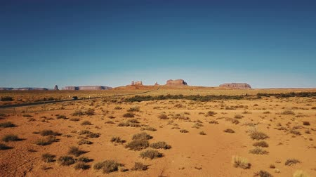 Drone flying low above dry American sandstone desert near Monuments Valley in Arizona and Utah, clear sunny blue sky.