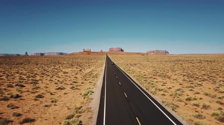 Drone follows car moving along iconic American desert highway road in Monuments Valley with big cliff mountains skyline.