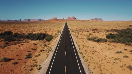 Drone flying backwards over iconic empty sandstone desert road in Monuments Valley, Arizona with big cliff mountains. Stock Footage