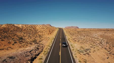 Drone rising up above car moving along empty desert road to reveal amazing mountain skyline in Monuments Valley, USA.