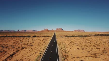 Drone follows silver car driving along famous sunny American desert highway road in Monuments Valley in Arizona and Utah Stock Footage