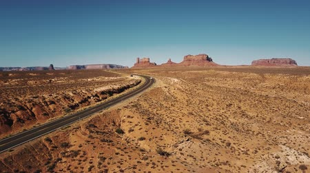 Cars passing by drone camera on desert highway road at sunny Monuments Valley in USA with amazing flat mountain skyline. Stock Footage