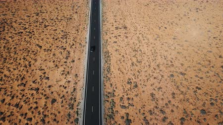 Drone follows silver car driving along dry American desert landscape highway, concept of global warming and erosion. Stock Footage