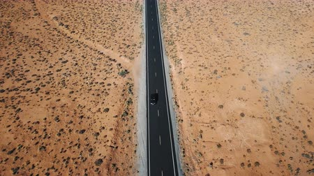 Aerial view of car driving along highway in the middle of American desert with beautiful natural landscape patterns.