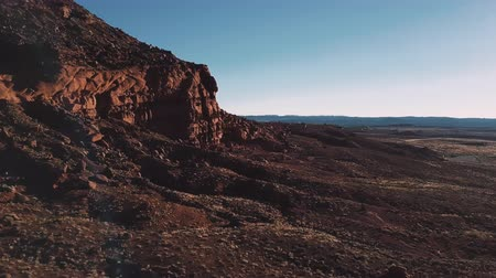 daleko : Drone flying next to massive cliffs and rocks in Arizona, incredible endless vast open spaces of sunny desert skyline.