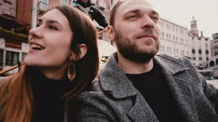 Close-up shot of happy smiling young European romantic couple in gondola enjoying Venice canal tour excursion in Italy. Stock Footage