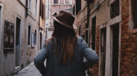 Back view of confident stylish young businesswoman in hat and suit walking along narrow ancient street in Venice, Italy.