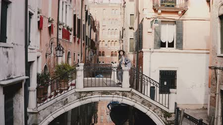 Beautiful perspective view of female tourist with camera walking on bridge over water canal street in Venice, Italy. Stock Footage