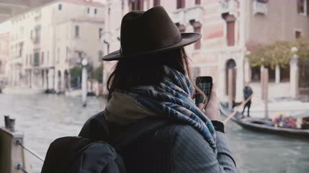 Happy attractive Caucasian businesswoman taking smartphone photos on a gondola excursion tour during Venice vacation. Stock Footage