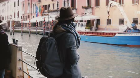 Camera tilts down on happy peaceful woman tourist enjoying atmospheric gondola canal excursion tour in Venice Italy.
