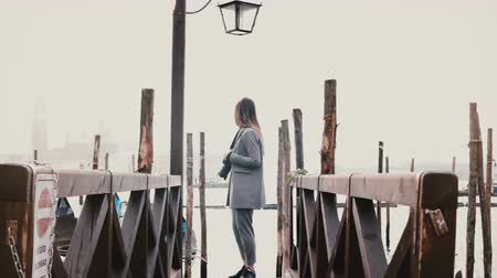 Венеция : Cinematic wide shot of happy beautiful woman with camera enjoying perfect travel moments on romantic Venice gondola pier