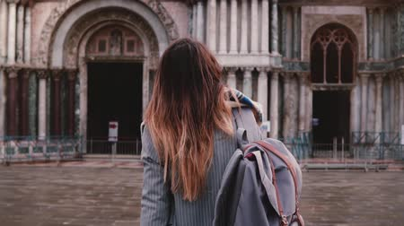 Beautiful woman tourist with backpack walking to amazing old antique building in Venice, Italy, looking back slow motion