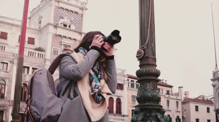 Beautiful female professional journalist with camera taking photos of old town in Venice Italy, smiling slow motion.