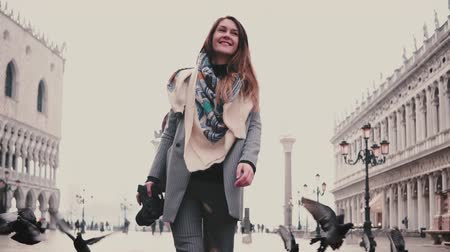 Happy beautiful female tourist with camera walks on San Marco square with flock of pigeons around in Venice slow motion