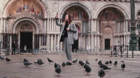 Happy excited female tourist with pigeon sitting on arm takes smartphone photos on city square in Venice slow motion.