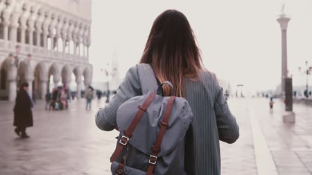 Beautiful young woman walking on amazing St Mark city square in Venice, Italy, touching hair back view slow motion.