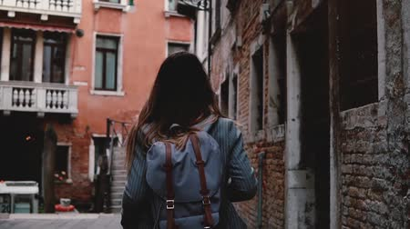 Camera follows young female tourist with backpack walking along beautiful dark ancient city street in Venice slow motion