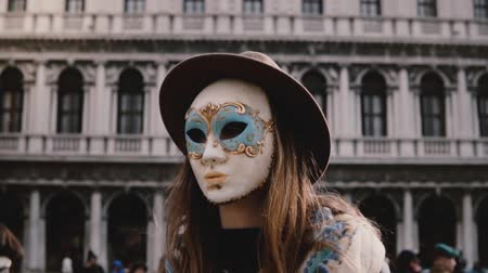 deguisement : Close-up shot of beautiful female tourist wearing traditional carnival mask at Venice San Marco square slow motion. Vidéos Libres De Droits