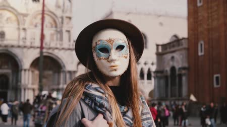 disguise : Female tourist with long hair posing in a traditional carnival mask standing at Venice San Marco city square slow motion