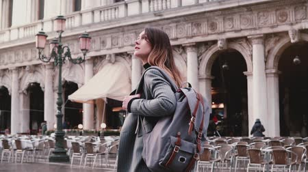 Happy young European businesswoman tourist enjoying walking along beautiful old San Marco city square in Venice, Italy. Stock Footage